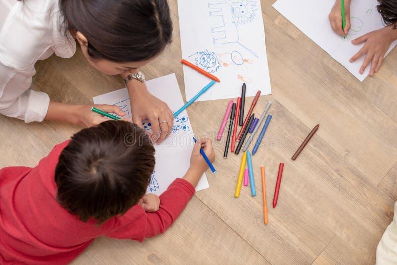 Grupa preschool ucznia i nauczyciela rysunek na papierze w sztuki klasie Popiera szko?a i edukaci poj?cie Ludzie i styl ?ycia zdjęcia royalty free