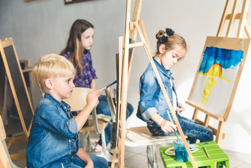 Grupa preschool ucznie i m?ody nauczyciel w rysunkowej klasie malujemy w guaszie mieszany biegowy uczennicy afroamerican zdjęcia royalty free