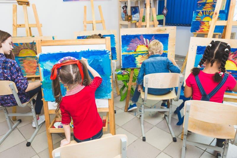 Grupa preschool ucznie i m?ody nauczyciel w rysunkowej klasie malujemy w guaszie mieszany biegowy uczennicy afroamerican obrazy stock