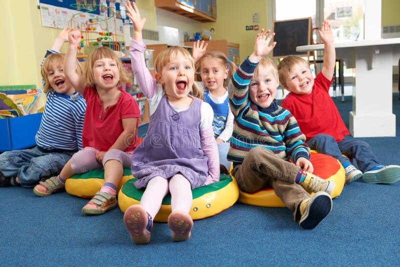 Grupa Przedszkolni dzieci Odpowiada pytanie W sala lekcyjnej fotografia royalty free
