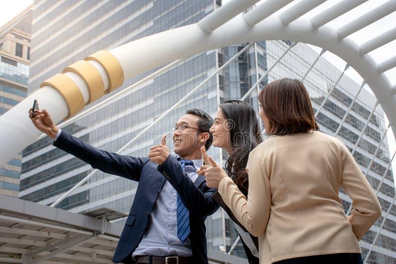Grupa przyjaciół rozochoceni pracownicy bierze jaźń portret z smartphone, partnerami biznesowymi/strzela selfie zdjęcia stock
