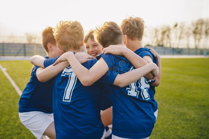 Grupa przyjaciół szczęśliwi dzieciaki w szkolnej sport drużynie Ch?opiec zbiera zabaw? na sporta polu i ma Rozochoceni dziecko ch fotografia stock