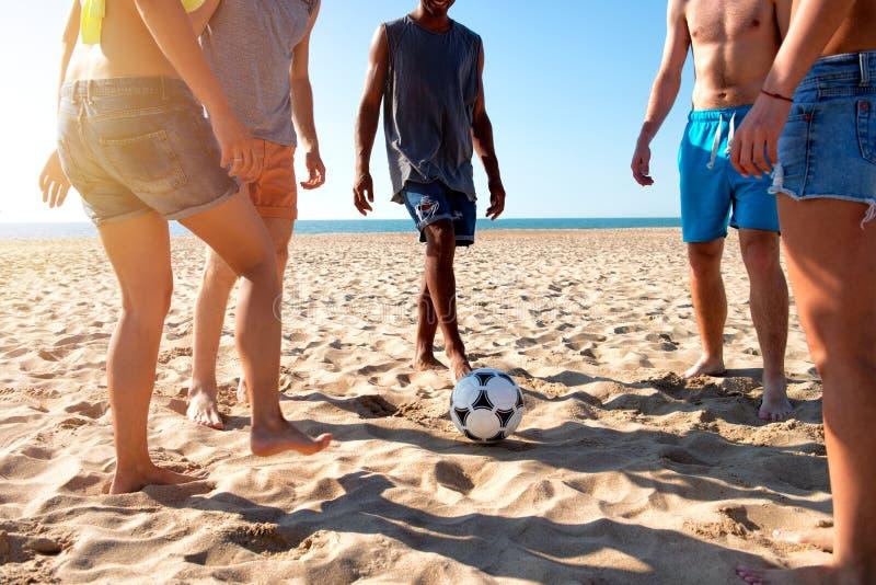 Grupa przyjaciele bawić się piłkę nożną przy plażą fotografia stock