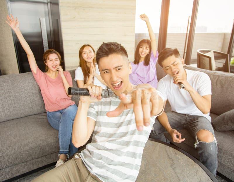 Grupa przyjaciele bawi? si? karaoke w domu obraz stock