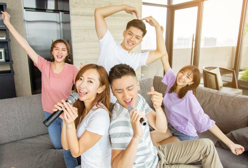 Grupa przyjaciele bawi? si? karaoke w domu obraz royalty free