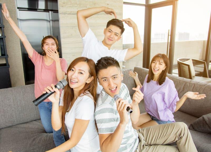 Grupa przyjaciele bawi? si? karaoke w domu zdjęcia royalty free