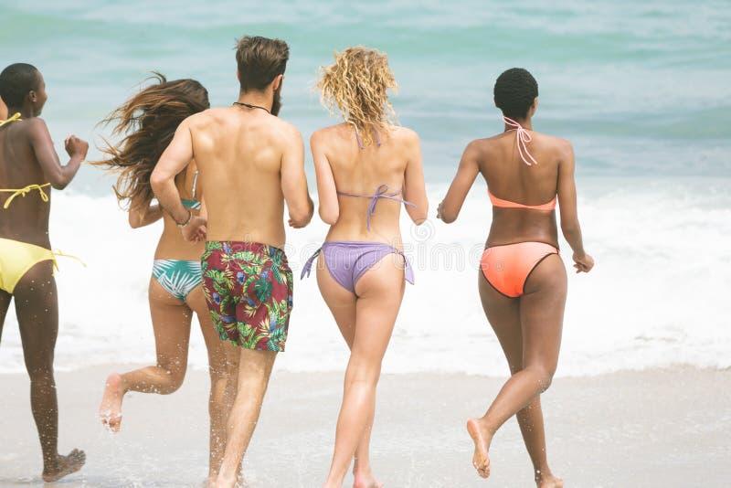 Grupa przyjaciele biega przy plażą zdjęcia stock