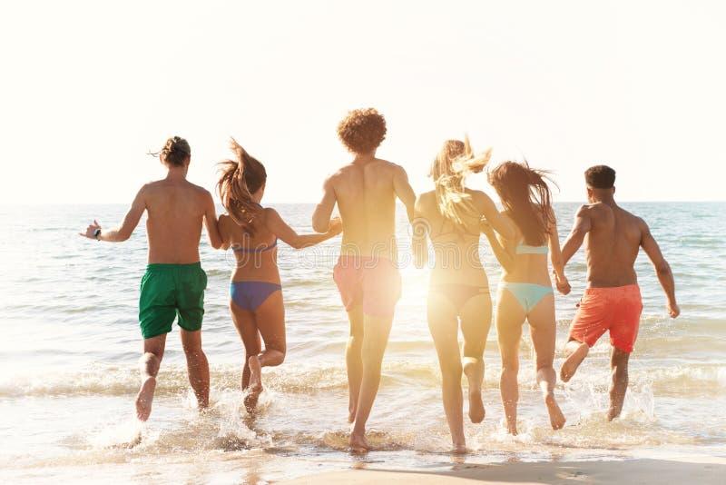 Grupa przyjaciele biegaj?cy w morzu Poj?cie lato fotografia stock