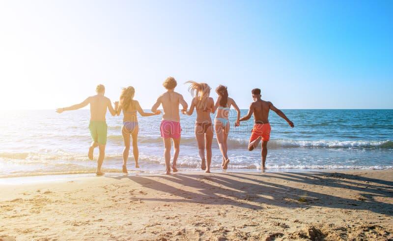 Grupa przyjaciele biegaj?cy w morzu Poj?cie lato obraz royalty free