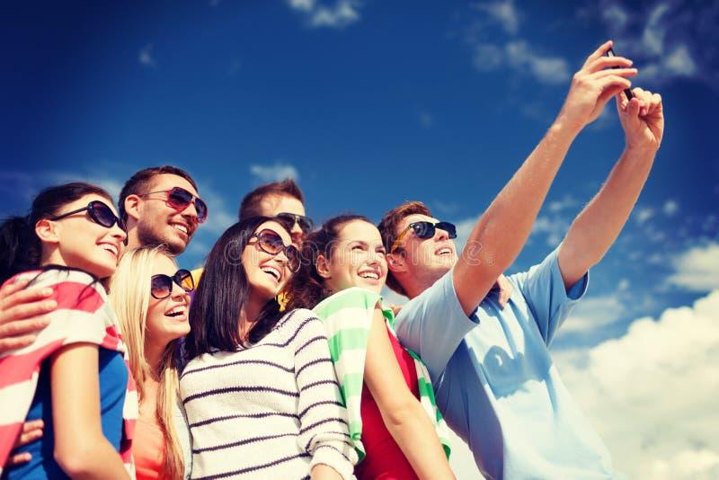 Grupa przyjaciele bierze obrazek z smartphone zdjęcia royalty free