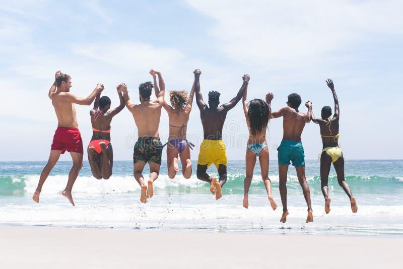Grupa przyjaciele cieszy się i skacze w wodzie przy plażą na słonecznym dniu zdjęcie stock