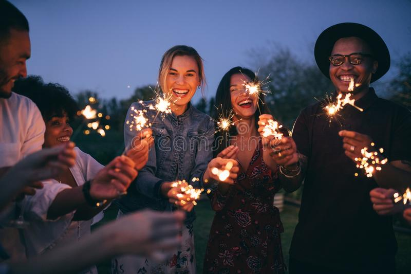 Grupa przyjaciele cieszy się out z sparklers zdjęcia stock
