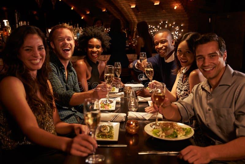 Grupa przyjaciele Cieszy się posiłek W restauraci obrazy stock