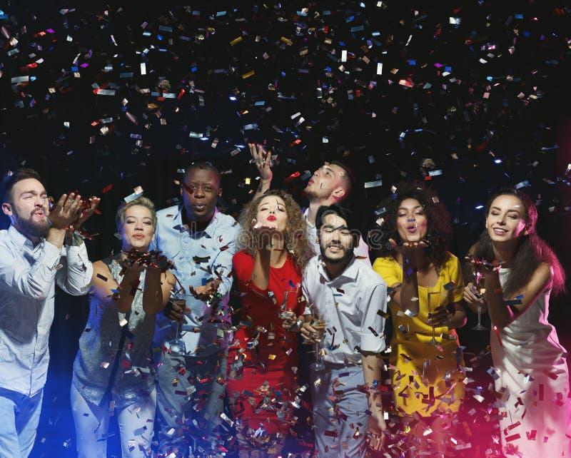 Grupa przyjaciele cieszy się przyjęcia i podmuchowych confetti zdjęcie royalty free