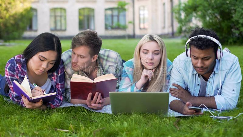 Grupa przyjaciele kłama na gazonie na kampusie i przygotowywa dla testa, studencki życie obrazy royalty free