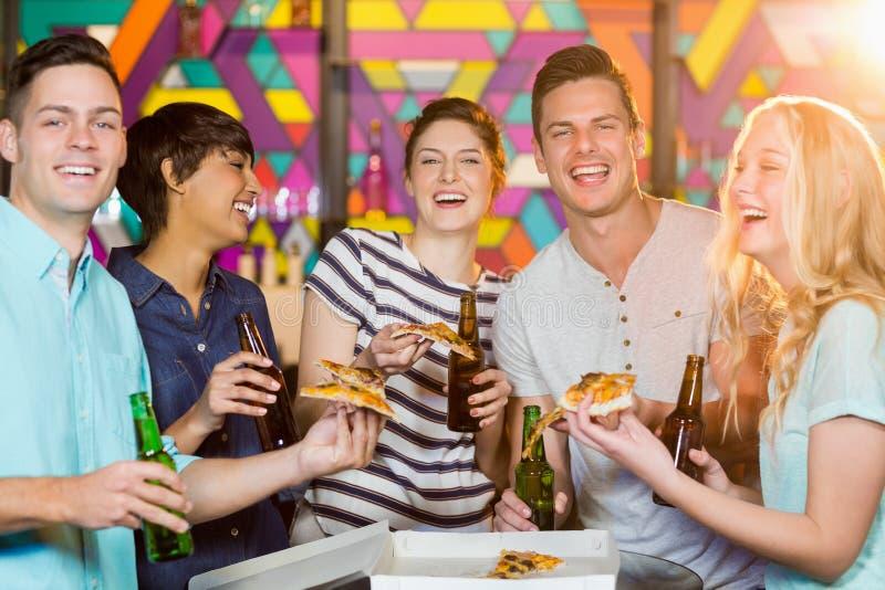 Grupa przyjaciele ma butelkę piwo i pizza w przyjęciu zdjęcia royalty free