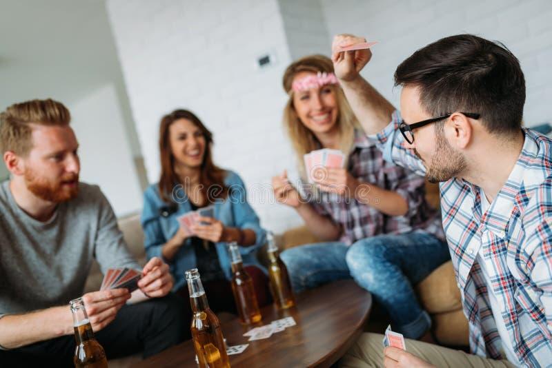 Grupa przyjaciele ma zabawę podczas gdy karta do gry zdjęcie royalty free