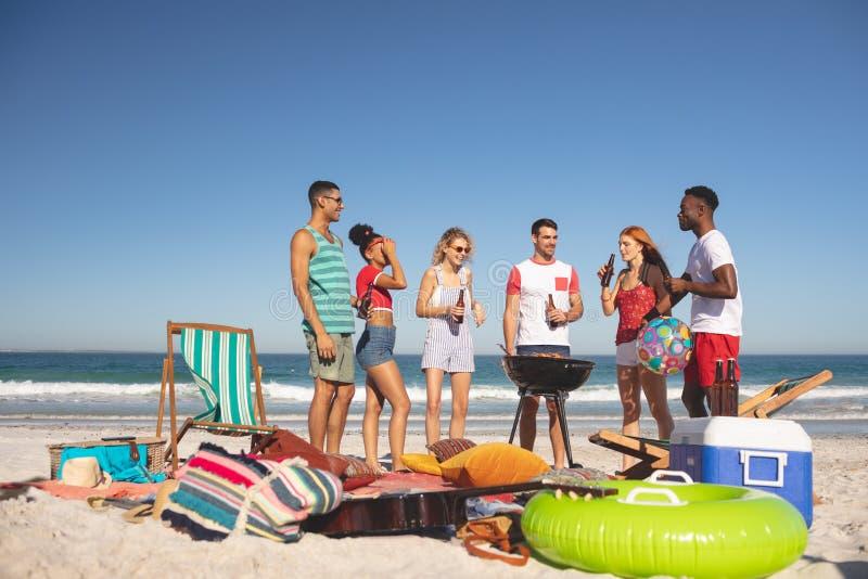 Grupa przyjaciele ma zabawę podczas gdy przygotowywający jedzenie na grillu przy plażą obrazy royalty free