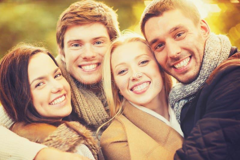 Grupa przyjaciele ma zabawę w jesień parku obrazy stock