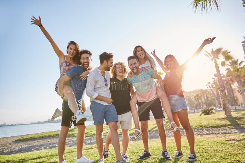 Grupa przyjaciele ma zabawę wpólnie outside w świetle słonecznym zdjęcia royalty free