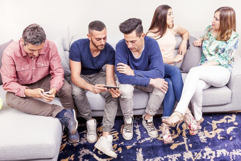 Grupa przyjaciele na leżanek spojrzeniach przy telefonem i opowiadać zdjęcie stock
