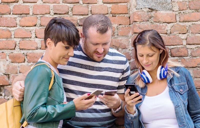 Grupa przyjaciele ogląda mądrze telefony komórkowych zdjęcia royalty free