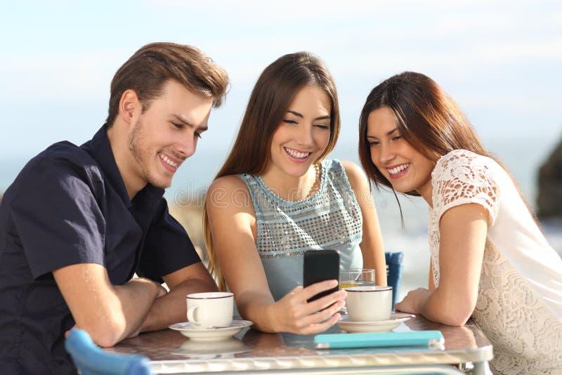 Grupa przyjaciele ogląda ogólnospołecznych środki w mądrze telefonie obraz royalty free