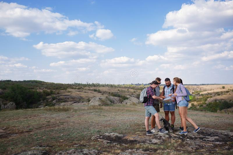 Grupa przyjaciele patrzeje mapę i dyskutuje outdoors Przyjaciele iść przy wycieczkować, las, odtwarzanie, miłość aktywnego styl ż zdjęcie royalty free