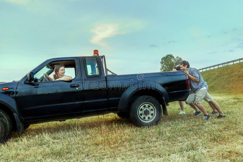 Grupa przyjaciele pcha łamanego samochód obrazy royalty free