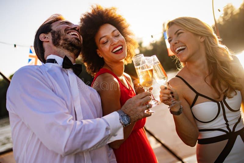 Grupa przyjaciele pije, gawędzi i ma zabawę przy plenerowym przyjęciem, zdjęcia royalty free