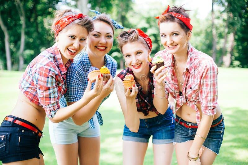 Grupa przyjaciele przy parkiem ma zabawy przyjęcia Rozochocone dziewczyny z torty w rękach styl retro zdjęcie stock