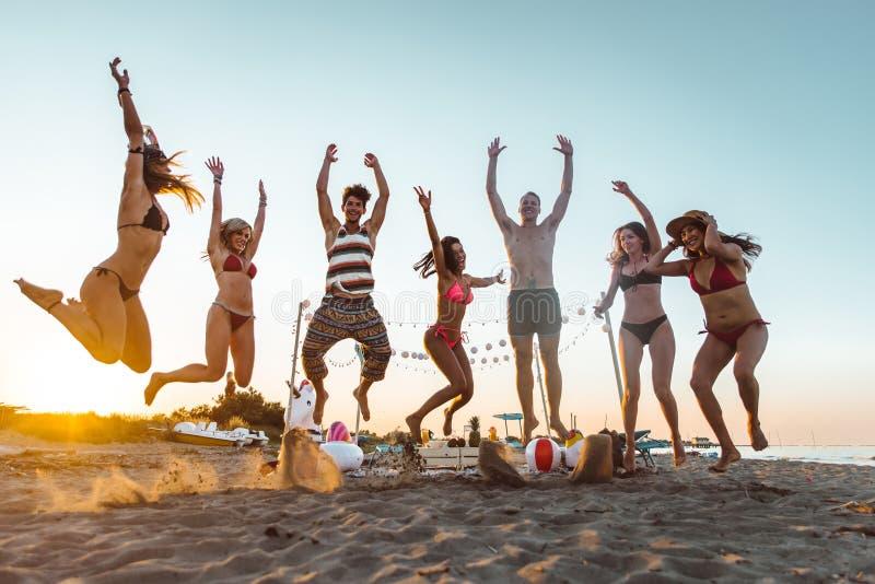 Grupa przyjaciele robi przyjęcia na plaży przy zmierzchu czasem obraz stock