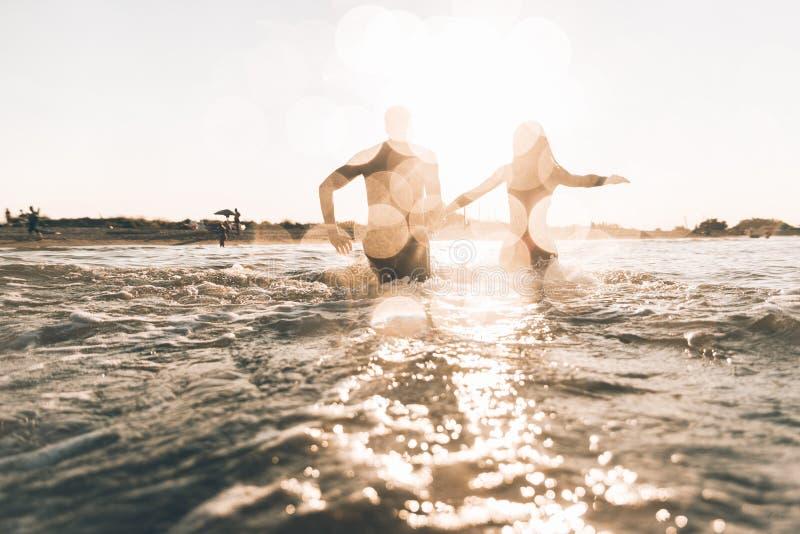 Grupa przyjaciele robi przyjęcia na plaży przy zmierzchu czasem fotografia royalty free