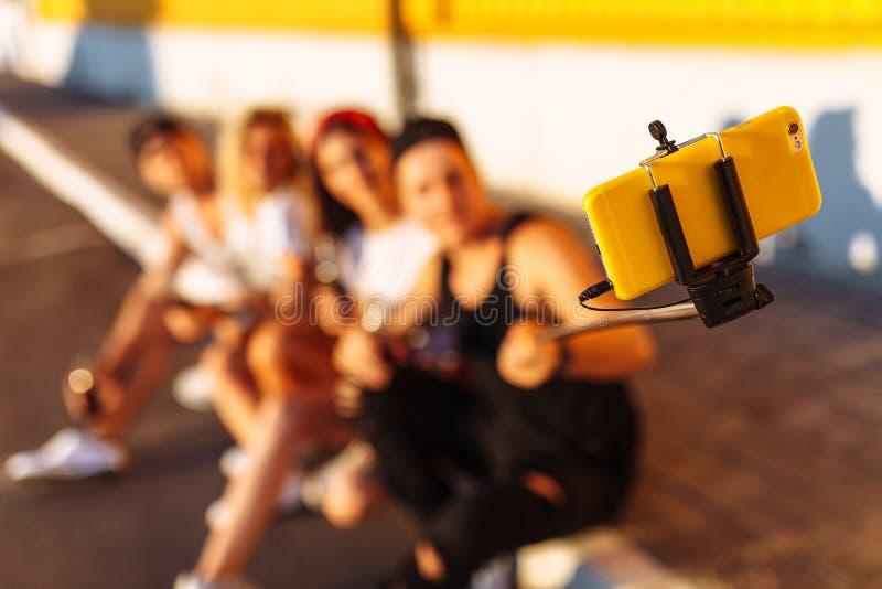 Grupa przyjaciele robi selfie obsiadaniu na bruku firma młodzi ludzie bierze obrazki z selfie kijem, cheerf fotografia stock