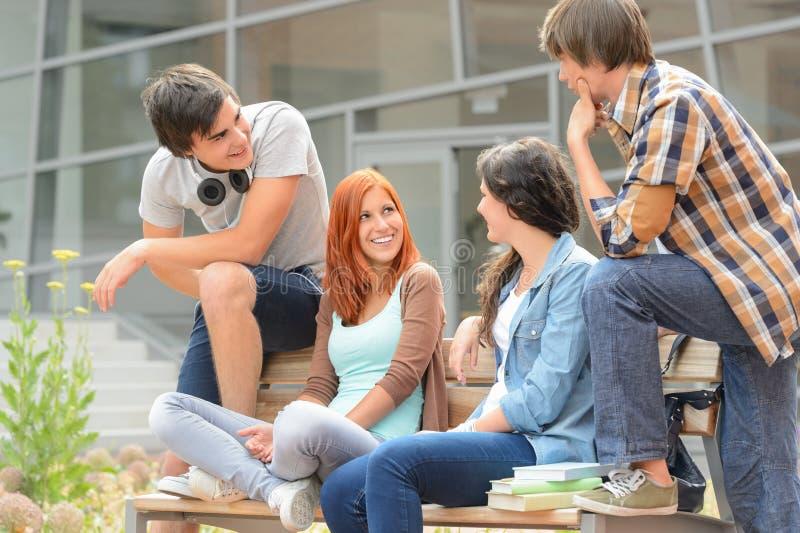 Grupa przyjaciele siedzi ławkę na zewnątrz szkoły wyższa obrazy royalty free