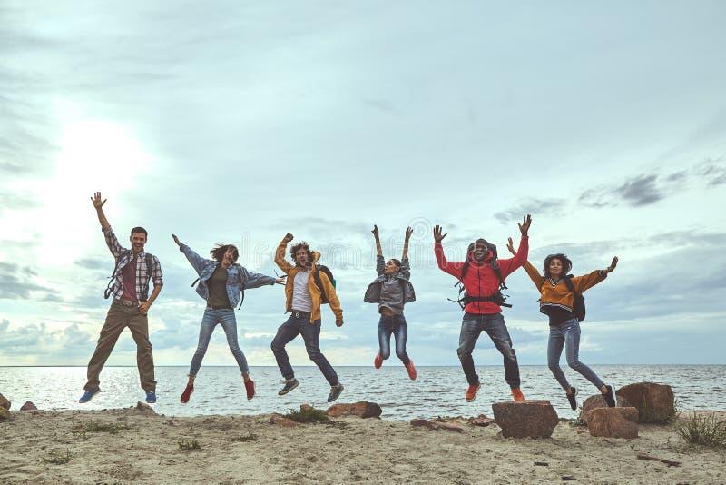 Grupa przyjaciele skacze na plaży zdjęcie stock