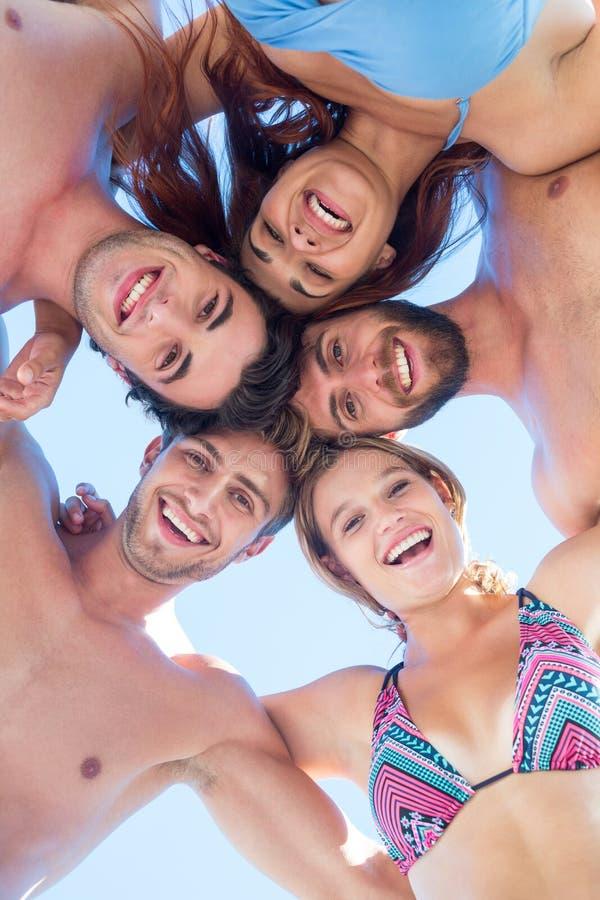 Grupa przyjaciele stoi w okręgu i ono uśmiecha się przy kamerą obrazy stock