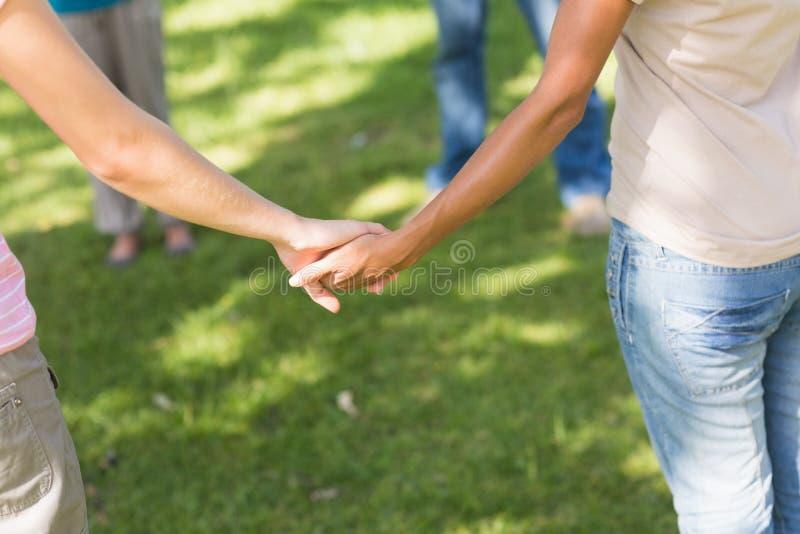 Grupa przyjaciele trzyma ręki w parku zdjęcia royalty free
