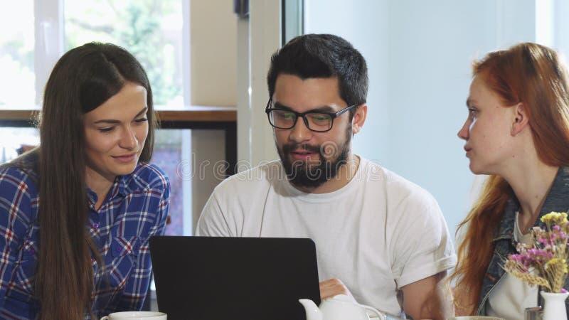 Grupa przyjaciele używa laptop przy sklep z kawą podczas gdy mieć śniadanie obrazy stock