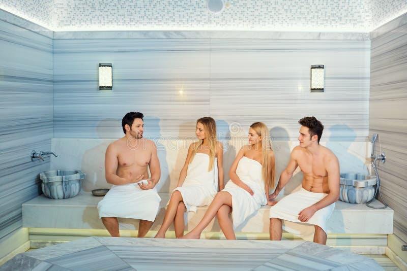 Grupa przyjaciele w ręcznikach śmia się przy sauna fotografia stock