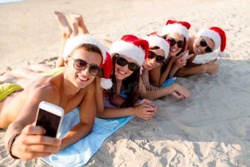 Grupa przyjaciele w Santa kapeluszach z smartphone fotografia stock