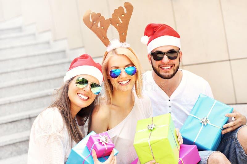 Grupa przyjaciele w Santa kapeluszach z teraźniejszość obraz stock