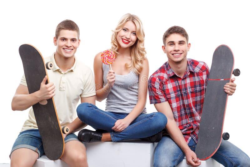 Grupa przyjaciele z deskorolka i cukierkiem zdjęcia stock