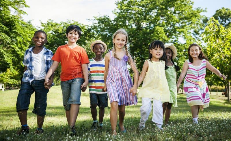 Grupa różnorodni dzieciaki ma zabawę w parku wpólnie obrazy royalty free