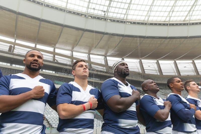 Grupa różnorodni męscy rugby gracze bierze przyrzeczenie wpólnie w stadium fotografia stock