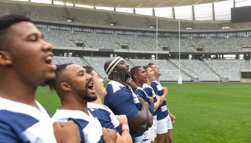 Grupa różnorodni męscy rugby gracze bierze przyrzeczenie wpólnie w stadium obrazy royalty free