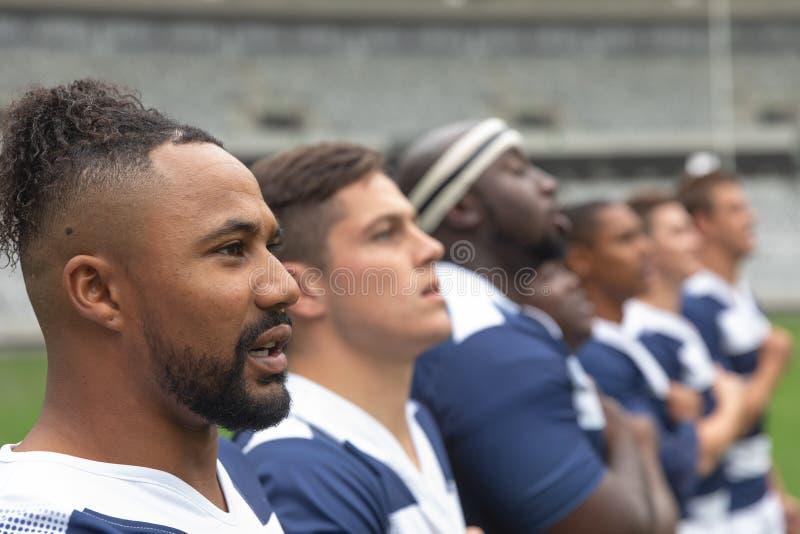 Grupa różnorodni męscy rugby gracze bierze przyrzeczenie wpólnie w stadium fotografia royalty free