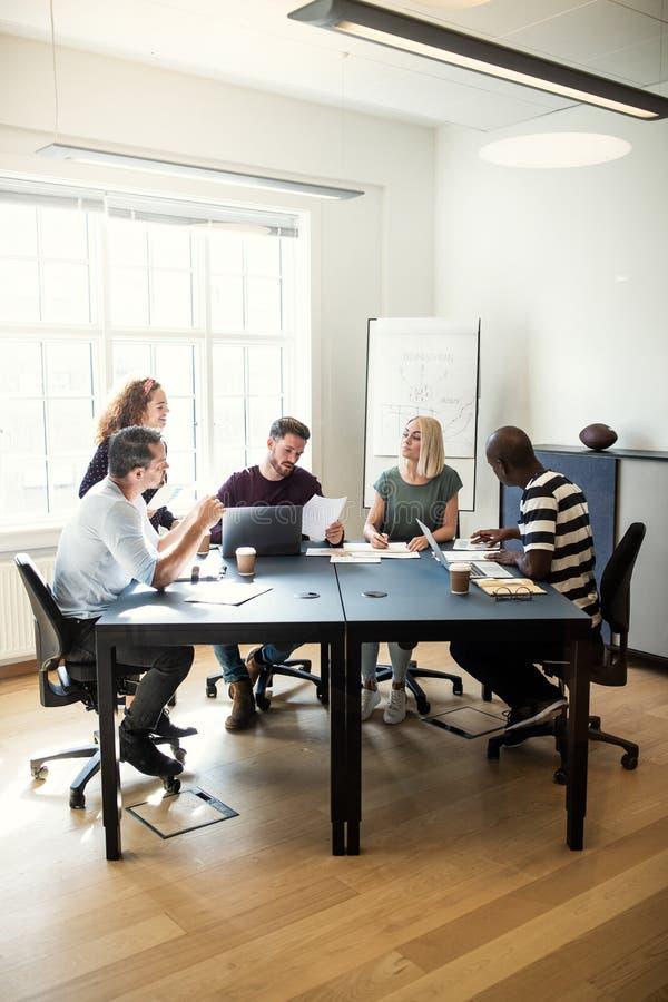 Grupa różnorodni projektanci opowiada wpólnie wokoło biurowej zakładki obraz stock