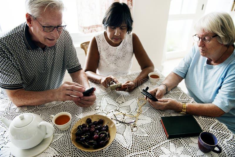 Grupa różnorodni starsi ludzie używa telefon komórkowego zdjęcia royalty free
