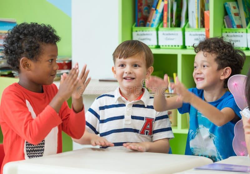 Grupa różnorodność dzieciaków chłopiec siedzi na stołowym wpólnie wewnątrz i bawić się zdjęcia stock